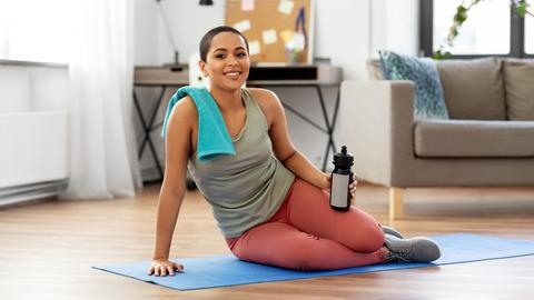 Eine junge Frau sitzt mit ihrer Trinkflasche und einem Handtuch auf einer Sportmatte.