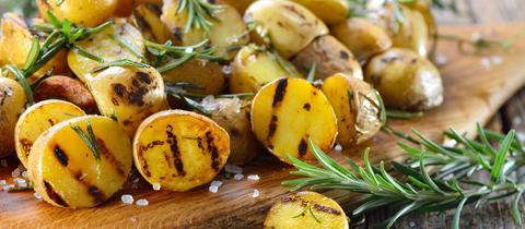 Kleine Rosmarin-Kartoffeln (Drillinge) mit grobem Salz auf Holzbrett angerichtet.