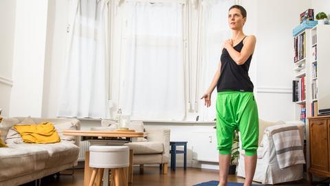 Eine Frau lässt steht in ihrem Wohnzimmer auf einer Sportmatte und lässt ihre rechte Schulter kreisen.