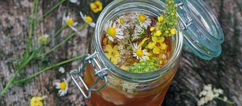 Selbstgemachter heller Wein mit Kräutern und Blüten in einem Glaskrug mit Verschluss.