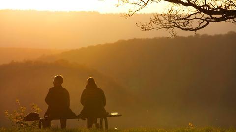 Zwei Touristen sitzen auf einer Bank und beobachten den Sonnenuntergang.