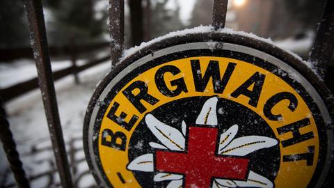 Das verschneite Bergwach-Logo auf dem von Schnee bedeckten Gipfelplateau des Großen Feldberges.
