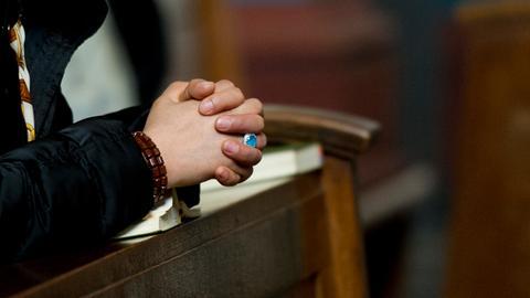 Eine Frau hat im Dom in Essen die Hände gefaltet.