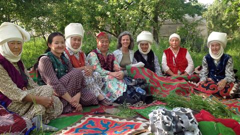 Kamerafrau Jenny Schenk in Mitten dorfansässiger Frauen in Jurten mit ihren tradionellen weissen Kopfbedeckungen.