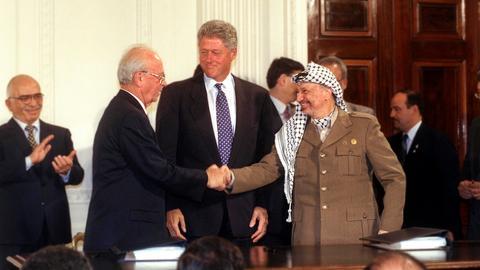 Rabin und Arafat geben sich nach der Unterzeichnung des Oslo II-Abkommens im weißen Haus (1995) die Hände.
