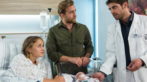Die frisch gebackenen Eltern Mia (Luise von Finkh, l.) und Paul Landauer (Jeremias Koschorz, M.) freuen sich über die Geburt ihrer Tochter Mathilda. Doch Dr. Niklas Ahrend (Roy Peter Link, r.) hat beunruhigende Nachrichten.