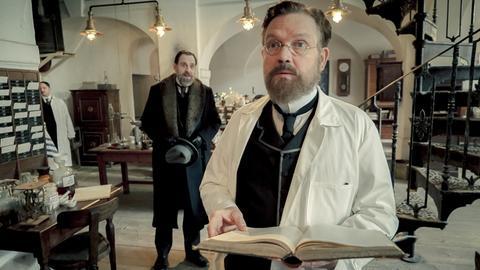Klinikdirektor Spinola (Thomas Loibl, l.) versucht Robert Koch (Justus von Dohnanyi, r.) davon zu überzeugen, am Kaiserempfang mitzuwirken.
