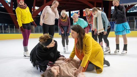 Solveig Dietze (Linda Stockfleth, liegend) ist beim Eiskunstlauf-Training gestürzt. Ihre Mutter Jutta (Judith Rosmair, li.) glaubt erst, dass sie simuliert. Doch als Arzu Ritter (Arzu Bazman, re.), die gerade mit ihren Söhnen zu einer Schnupperstunde vorbeischaut, bei Solveig ankommt, wird klar: Es ist ernst. Solveig muss sofort in eine Klinik.