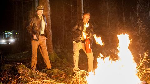 Hubert (Christian Tramitz, r.) und Staller (Helmfried von Lüttichau, l.) erreichen die Feuerstelle im Wald. Hubert versucht mittels des Feuerlöschers den Brand zu löschen.