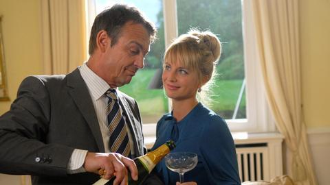 Grund zu feiern? Andersen (Krystian Martinek, l.) hat den Champagner für sich und seine Sekretärin (Doreen Nixdorf, r.) entkorkt und will ihr eben einschenken, als es an der Tür klingelt.