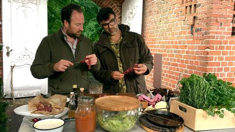 Tarik Rose und Fried Graf von Bernstorff begutachten ihr Essen genau.