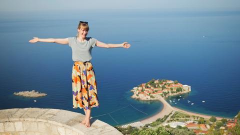 Frau steht an einer Klippe vor dem blauen Meer