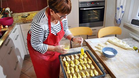 Oma Margarete Klenner streicht Eigelb auf die Flachswickel (Nachtisch).