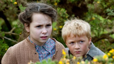Fiona (Chloe Jayne Wilkinson) und der kleine Brian (Haydn Cavanagh) beobachten das Treiben eines brutalen alten Bauern.