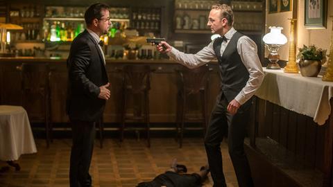 Prof. Harald Götz (Peter Jordan, r) schießt einen von Prof. Boernes (Jan Josef Liefers, l) Gästen nieder, dann bedroht der den Gastgeber selbst.