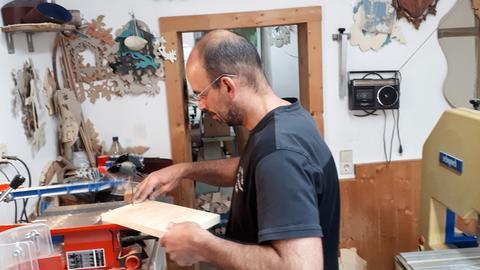 Der Holzbildhauer Oliver Zinapold sägt das ausgesuchte Holz weiter in Stücke, die den Maßen der späteren Kuckucksuhr schon annähernd entsprechen. Von Hand geführt arbeiten spezielle Sägen die ersten Facetten des künftigen Kunstwerks heraus. Als Laubsägen wird diese Arbeit bezeichnet. Aber mit Hobby-Basteleien hat das wenig zu tun.