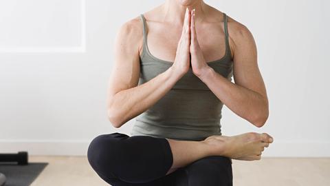 Eine Frau, die Yoga auf der Matte übt und nur mit einem Fuß am Boden ist.