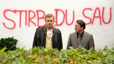 Nach einer bedrohlichen Wandschmiererei bittet Schuldirektor Höpfl (Robert Palfrader, re.) Polizeihauptmeister Franz Eberhofer (Sebastian Bezzel) um Hilfe.