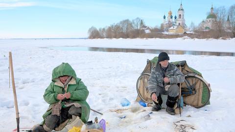 Seit dem frühen Morgen sitzen die Eisfischer auf dem zugefrorenen Nero-See. Im Hintergrund der Kreml von Rostov.