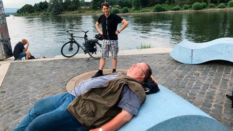 Danny Morgenstern (stehend) und sein Begleiter Holger Schulze legen auf ihrer Radreise eine Pause ein.