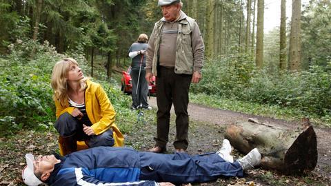 Baumarktinhaber Pfaff (Rolf Zacher, l.) wird beim Nordic Walking vor den Augen seiner Frau und eines Angestellten (im HG) erschossen. Mord oder Jagdunfall rätseln Sophie Haas (Caroline Peters, 2.v.l.) und Hans Zielonka (Michael Hanemann, r.).