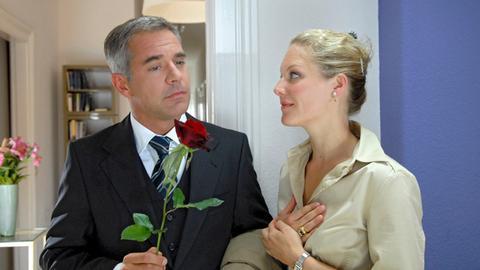 Lilo (Tessa Mittelstaedt, r.) ist gerührt, als Seibold (Florian Fitz, l.) ihr eine rote Rose zu ihrem Jahrestag überreicht.