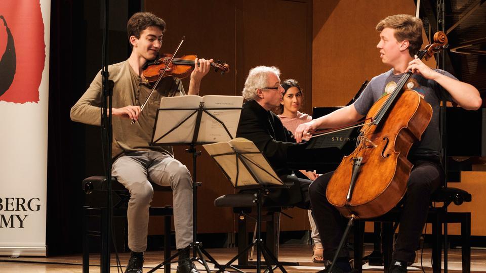 Der Violinist Stephen Waarts (links) und der Cellist Jonathan Roozeman (rechts); im Hintergrund am Flügel der Pianist András Schiff.