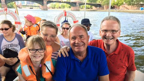 Holger Weinert (Mitte) mit Passagieren auf dem Kinderfeuerwehrboot in Frankfurt.