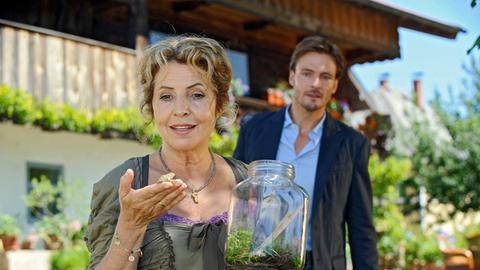 """Christian (Andreas Pietschmann) beobachtet, wie Teresa (Michaela May) einem """"Wetterfrosch"""" die Freiheit schenkt."""