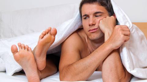 Ein junges Paar liegt frustriert unter der Bettdecke. Es sind nur die Füße der Frau zu sehen und ein frustrierter junger Mann, der unter der Bettdecke hervorschaut.
