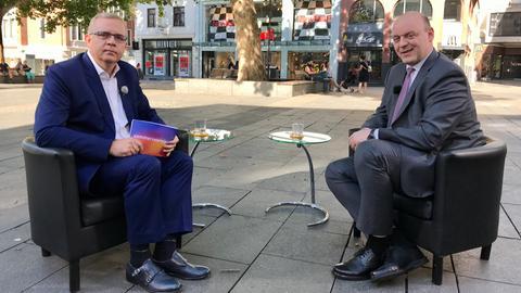 Michael Immel interviewt Robert Lambrou in einer Fußgängerzone.