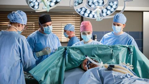 Milan Pavlovics (Manuel Krstanovic, v.) Zustand wird immer schlechter. Dr. Marc Lindner (Christian Beermann, 2.v.l. mit Komparsen), Julia Berger (Mirka Pigulla, 2.v.r.) und Tom Zondek (Tilman Pörzgen, r.) müssen um das Leben ihres Patienten bangen.