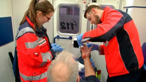 Die Sanitäter Maja Charlotte Heyden und Thomas Hose versorgen die blutende Wunde ihres Patienten.