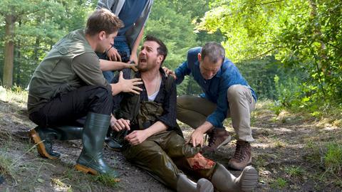 Dr. Hansen (Heikko Deutschmann) schaut sich die Bisswunde von Vinzenz Grieshaber (Michael Sideris) an. Pawel (Moritz Knapp) hinter ihnen. Links Tomasz (Adrian Topol) versucht Grieshaber zu beruhigen.
