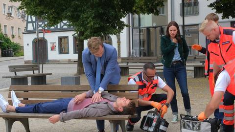 Dr. Timotheus von Hatzfeld (Tom Radisch, l.) leistet erste Hilfe bei David Pankow (Constantin Lücke, M.), den Exfreund von Dr. Carolin Thelen (Diane Willems, r.).
