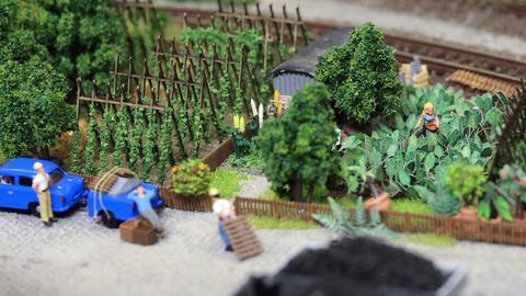 Die Figuren einer Kleingärtnerin und Arbeitern stehen auf einer Miniaturlandschaft einer privaten Modelleisenbahnplatte in Magdeburg.