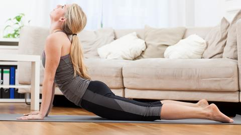 Eine junge Frau führt in einer Wohnung die Yoga-Übung Kobra aus.