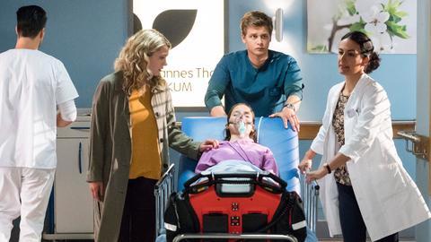 Dr. Leyla Sherbaz (Sanam Afrashteh, r.) und Mikko Rantala (Luan Gummich, h.M.) bringen die bewusstlose Sophia Krämer (Bianca Nawrath, v.M.) in den OP. Pia Krämer (Charleen Deetz, 2.v.l. mit Komparse, l.) begleitet ihre Schwester, so lange es geht.