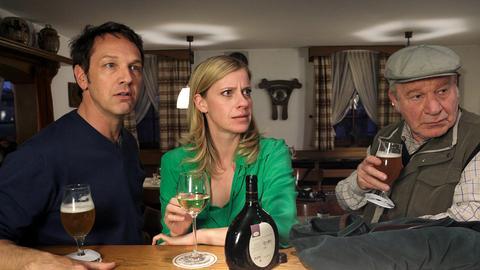 Sophie Haas (Caroline Peters, M.) muss ihrem Vater zuliebe in Hengasch bleiben und trifft sich mit Andreas Zielonka (Max Gertsch, l.) und dessen Vater Hans (Michael Hanemann, r.) im Gasthof. Doch die Runde wird durch eine Neuigkeit aufgeschreckt.