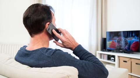 Ein Mann sitzt in einem Wohnzimmer und schaut Fernsehen, während er dabei telefoniert.