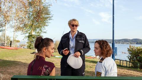 Nele Fehrenbach (Floriane Daniel, M.) und Julia Demmler (Wendy Güntensperger, r.) sprechen mit Catrin Dellbrück (Maddalena Noemi Hirschal, l.), der Witwe des ermordeten Wassersportlehrers.