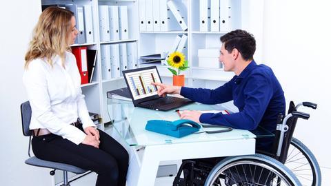 Ein Mann im Rollstuhl zeigt seiner Kollegin eine Folie mit Statistiksäulen auf seinem Laptop im Büro.