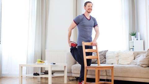 Ein junger Mann macht in einer Wohnung Fitnessübungen an einem Stuhl.