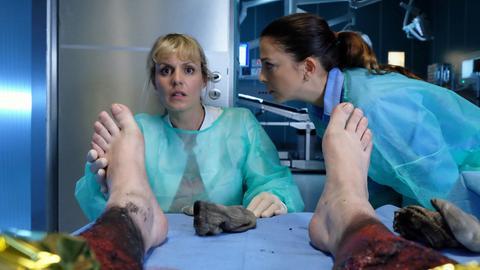 Dr. Lea Peters (Anja Nejarri, li.) entdeckt bei der Untersuchung eines schwerst Brandverletzten eine Narbe, die von einem Blitzschlag stammt. Lea wird bewusst, dass es sich bei dem Mann um ihren Freund Jenne handelt. Oberschwester Arzu erstarrt bei dem Gedanken.