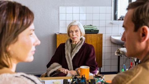 Martin Koslowski (Sönke Möhring, r.) und Tina (Anna Grisebach, l.) hören sich die Geschichte von Gerda Langer (Dagmar von Kurmin, M.) an. Diese bittet Martin um Personenschutz, denn sie glaubt, dass ihre Schwester Elisabeth ihr nach dem Leben trachtet.