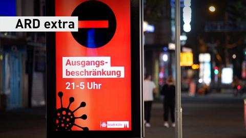 Ein Bildschirm weist auf die Ausgangsbeschränkung von 21-5 Uhr hin. Schriftzug: ARD Extra.