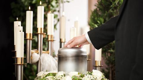 Beisetzung mit Urne, Blumen und Kerzen