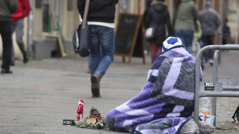Armut in Deutschland - Bettelnder wohnungsloser Mann mit einer kleinen Weihnachtsdeko in der Adventszeit im Bereich eines Einkaufszentrums bittet Passanten um Spenden.