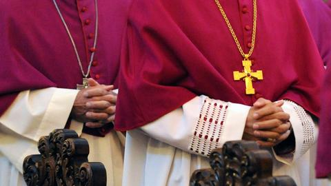 Bischöfe haben die Hände gefaltet.