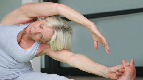 Eine Seniorin macht Pilates-Übungen.